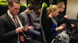 Commuters looking at their phone