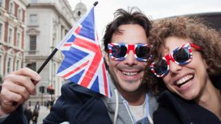 couple with union jack glasses and flag