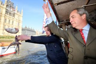 Nigel Farage and Aaron Brown symbolically dump fish into the River Thames.