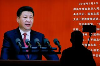 A man takes a selfie near a picture of Chinese President Xi Jinping on display at an exhibition on the Long March at the military museum in Beijing, Monday, 24 October 2016.