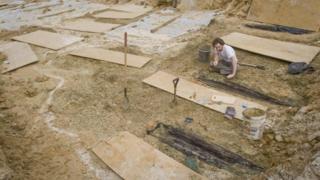 Investigador desenterrando ataúdes.