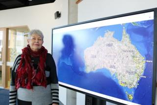 Professor Lyndall Ryan with a screen showing a map of Australia's frontier massacres