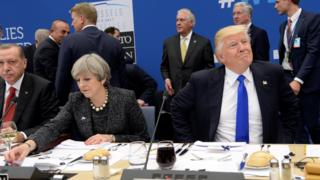 "US President Donald Trump (R) reacts as he sits next to Britain""s Prime Minister Theresa May (C) and Turkish President Recep Tayyip Erdogan (L) during a working dinner meeting at the NATO summit in Brussels, Belgium, 25 May 2017"