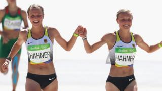 Anna Hahner (L) of Germany and her sister Lisa Hahner approach the finish line during the Women's Marathon on Day 9 of the Rio 2016 Olympic Games at the Sambodromo on 14 August 2016 in Rio de Janeiro, Brazil
