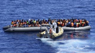 Migrants sit in their boat during a rescue operation by Italian Navy vessels off the coast of Sicily (11 April 2016) (Italian Navy handout)