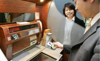 Man stands in front of a Japanese ATM, holding a Shinsei bank card, as a member of bank staff looks on