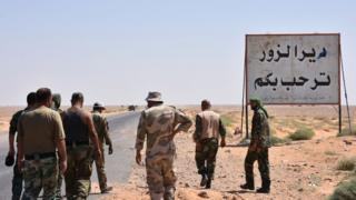 """Syrian government forces stand beside a sign saying """"Welcome to Deir al-Zour"""" in eastern Syria on 3 September 2017"""
