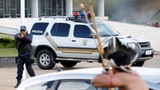Protesto sırasında bir polis memurunun silah doğrulttuğu yerli, karşılık olarak okunu geriyor.