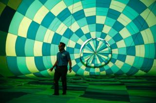 A staff member inspects the interior of a hot air balloon