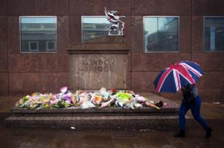 A member of the public passes flowers and tributes left for victims of the London Bridge terror attacks