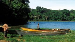 Hombres en las islas Ssese, frente a un bote