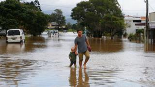 A man and a young boy walk through shallow floodwaters.