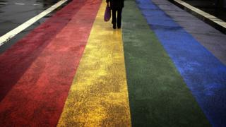 Man stands on rainbow flag pavement ahead of Gay pride Sydney in 2013