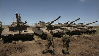 Israeli soldiers stand by Merkava tanks on the occupied Golan Heights