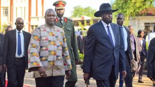 Riek Machar walks alongside President Salva Kiir on the red carpet