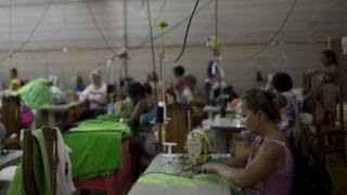 Mulher trabalha em fábrica de roupas
