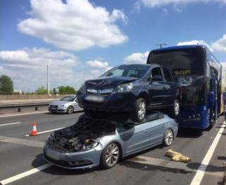 Car on top of another car in front of a crashed coach