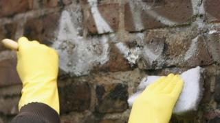 People cleaning a wall on a community payback scheme