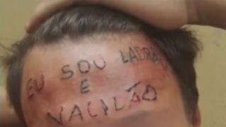 """Tattoo on the boy's forehead reads """"I'm a thief and loser"""""""