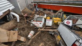 قدرت سیل کامیونها را به دیوار خانهها کوبیده است.