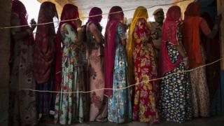 Indian women wait to vote at a polling station on April 17, 2014 in the Jodhpur District in the desert state of Rajasthan, India. India is in the midst of a nine-phase election that began on April 7 and ends on May 12.