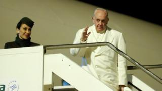The Pope waves as he boards a plane bound for Myanmar