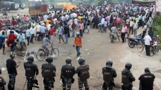 Nepalese policemen face protestors belonging to ethnic and religious groups dissatisfied with Nepal's new constitution adopted on Sunday