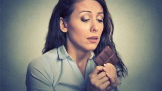 Mujer tentada de comer chocolate