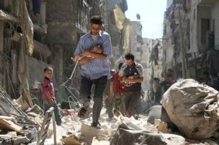 Halep'te bir hava saldırısının ardından aileler, yıkılan binaların enkazının arasından yürüyor.