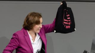 """The deputy chair of the parliamentary group of the right-wing Alternative for Germany (AfD) party Beatrix von Storch presents a bag reading """"AfD? Appropriate disposal of right-wing agitation!"""" of the confederation """"Standing up against racism"""" during a session of the German parliament """"Bundestag"""" in Berlin, Germany, 13 December 2017. D"""