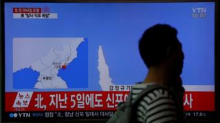 Passenger at railway station in Seoul walks past TV news report of failed missile launch