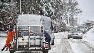 Workers trying to push a van during snowy conditions in Scotland