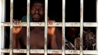 Two migrant men are pictured in detention in Gharyan, Libya