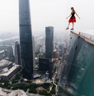 Angela Nikolau dangling her foot over the edge of a high rise building