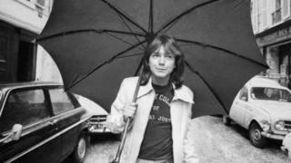 David Cassidy caminando en una calle de Londres con un paraguas (30 de abril de 1974)