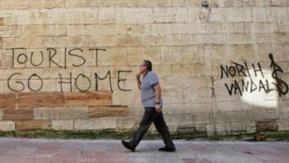 """A man walks past a """"Tourists Go Home"""" graffitti on a wall close to the City Hall in Oviedo, northern Spain,"""