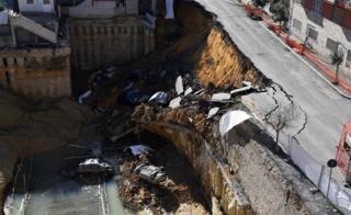 A huge sinkhole swallows six cars.