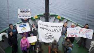 Clyde River residents hold up anti-seismic blasting signs on the bow of the Arctic Sunrise, during a ship tour