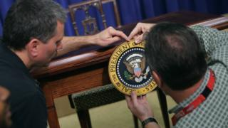 Workers affix the US presidential seal on a desk in the White House