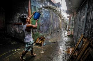 A man uses a bucket to help put out the fire in a small shop in the Mercado Oriental, where approximately 25 stores were completely burned in one of the largest markets in Central America, in Managua on May 14, 2017. /