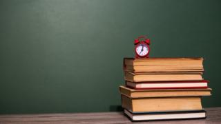 Reloj diminuto sobre libros y tablero