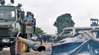 Security personnel sitting on a truck watch burned vehicles at the front gate of the Makala prison after it was attacked by supporters of jailed Christian sect leader Ne Muanda Nsemi in Kinshasa, Democratic Republic of the Congo May 17, 201