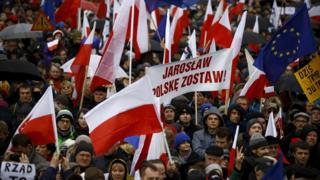 """People hold up a banner that reads, """"Jaroslaw (Kaczynski) leave Poland"""", during an anti-government demonstration in front of the Constitutional Court in Warsaw, Poland"""