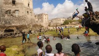 Watoto wa kisomali wanaogelea na kucheza mbele ya magofu ya nyumba ya zamani katika pwani ya Hamarweyne, jijini Mogadishu Ijumaa.