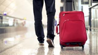 Man walking at an airport with a suitcase