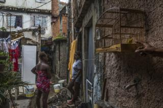 Women waiting in one of the alleyways while they fill up their water buckets. Favela Vila do Metro community, Mangueira, Rio de Janeiro, Brazil