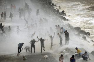 Una multitud se divierte con las olas que alcanzan el malecón de Bombay, India.