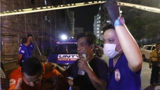 Сотрудники экстренных служб эвакуируют пострадавшего из отеля в Маниле, атакованного неизвестным