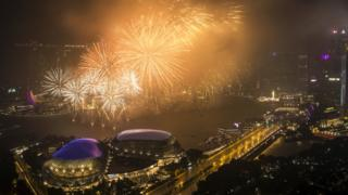 New Year Eve's fireworks illuminate the skyline of the Marina Bay Sands resort (back-L), the Esplanade Theatres (front-L), and the financial district (R) around the Marina Bay in Singapore, 01 January 2018.