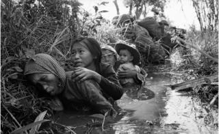 Women and children crouch in a muddy canal as they take cover from intense Viet Cong fire at Bao Trai, about 20 miles west of Saigon, Vietnam, on 1 January 1966.